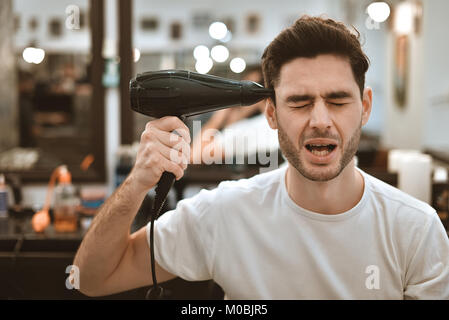 Young crazy stylish man with hair dryer and funny expressions in the barbershop. - Stock Photo