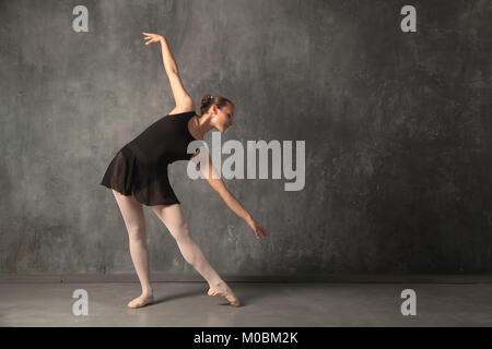Beautiful attractive blonde woman baterina in a black dance tutu, white pantyhose and pointe shoes dancing in a - Stock Photo