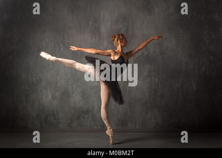Beautiful attractive blonde woman primer ballerina in a black dance pack, white pantyhose and pointe shoes beautifully - Stock Photo