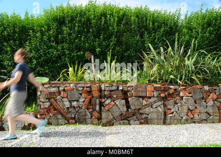 A woman in her mid fifties runs on a crushed concrete path beside gabions filled with building rubble and metal - Stock Photo