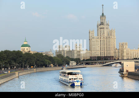 Moscow, Russia - July 31, 2010: Trip boat on Moscow river against one of Seven Sisters in Moscow, Russia on July 31, 2010