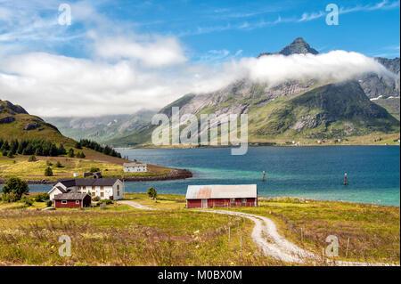 Traditional farm buildings in coast landscape on Lofoten islands in northern Norway. Lofoten is a popular tourist - Stock Photo