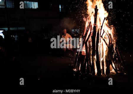 A man tending to huge bonfire at Kurama fire festival, Mount Kurama, Kyoto, Japan