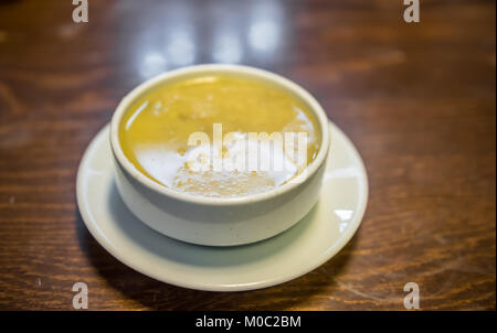 Traditional Turkish hot Tripe Soup served on wooden table. - Stock Photo