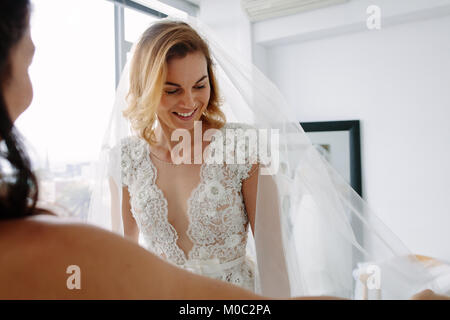 Beautiful young woman trying on wedding dress in bridal shop with assistant. Future bride fitting new dress in wedding - Stock Photo