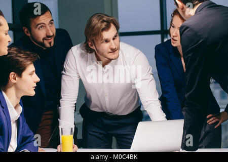 Smiling Female And Handsome Male Co-Workers Sitting At Table, Looking At Laptop - Stock Photo
