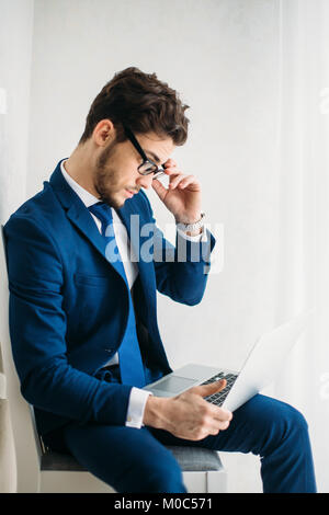 Young businessman working with laptop at office - Stock Photo