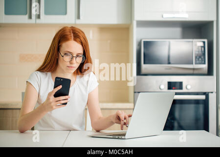 woman sitting in kitchen and holding phone while using laptop - Stock Photo