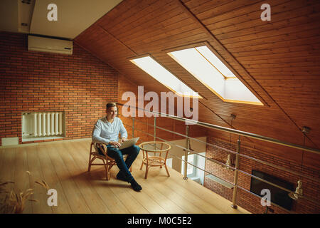 man sitting at home and working on laptop. male working from loft home office - Stock Photo
