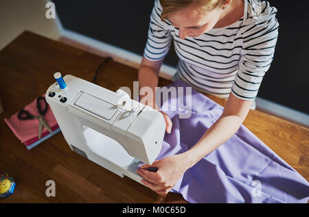 Overhead view of creative woman with sewing machine - Stock Photo