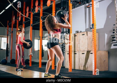Two women throws medicine balls in fitness gym - Stock Photo