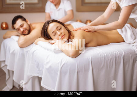Happy couple getting massage at spa - Stock Photo