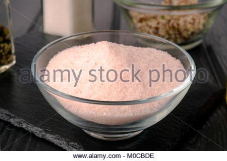 pink salt of the himalayas, on black slate dish - Stock Photo