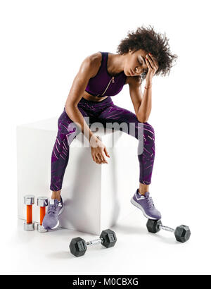 Headache. Sporty african girl is tired after intense workout on white background. Health concept. - Stock Photo