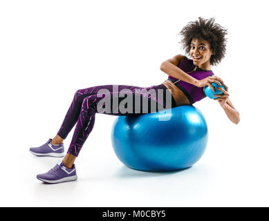 Smiling sporty girl doing fitness exerrcise on gymnastic ball. Photo of young african girl in sportswear on white - Stock Photo