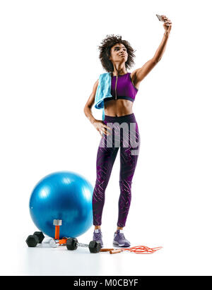 Sporty girl taking selfie pictures on smartphone with sports accesories on white background. Strength and motivation. - Stock Photo