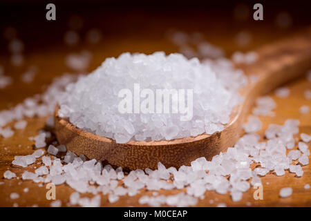 Sea salt crystals closeup in wooden spoon on a kitchen table. - Stock Photo
