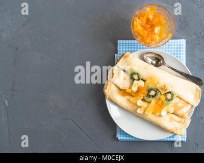 Delicious pancakes with banana, kiwi and orange - Stock Photo