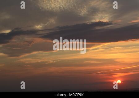 The sun begins to rise on a cloudy stormy day giving us this colorful angry sky - Stock Photo