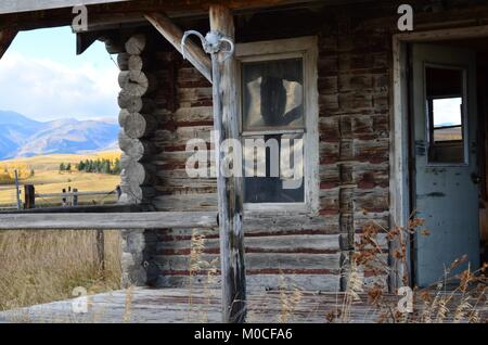Here sits an old abandoned log cabin, in the middle of a field with a wonderful porch view of the mountains and - Stock Photo