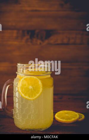 Fresh lemonade in mason jar and lemon slices on wooden background - Stock Photo