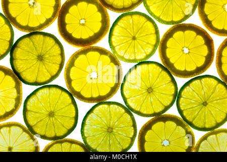 Background of backlit fresh lemon and lime slices - Stock Photo