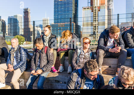 New York City, USA - October 27, 2017: People sitting on wooden benches on highline, high line, urban in NYC with - Stock Photo