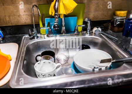 Closeup of dirty dishes in stainless steel sink kitchen by cleaning tools, cutting boards, brick wall - Stock Photo