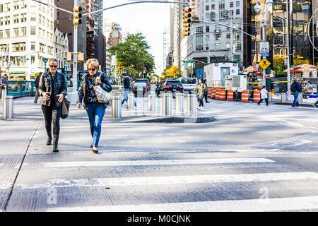 New York City, USA - October 28, 2017: Two women talking walking crossing Columbus Circle street road in Midtown - Stock Photo