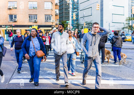 New York City, USA - October 28, 2017: Midtown Manhattan with crowd crowded many people crossing street of 59, Columbus - Stock Photo