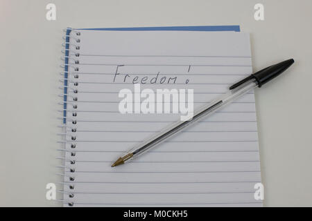 Handwriten Freedom on notepad - Stock Photo