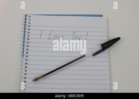 Handwriten 'I love you' on notepad - Stock Photo