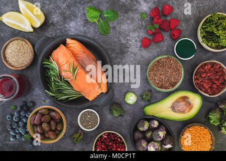 Fish with fresh healthy food ingredients featuring seeds, legumes, fruits and vegetables. Top view, blank space, - Stock Photo