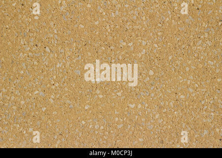 Sand colored tan stucco wall background with exposed stones on its surface - Stock Photo