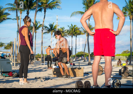 MIAMI - DECEMBER 29, 2017: Muscular young men and women work out in the outdoor gym known as Muscle Beach in Lummus - Stock Photo