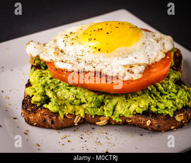 Avocado toast on white plate made with whole grain bread, sunny side up fired egg, and a sliced tomato. - Stock Photo