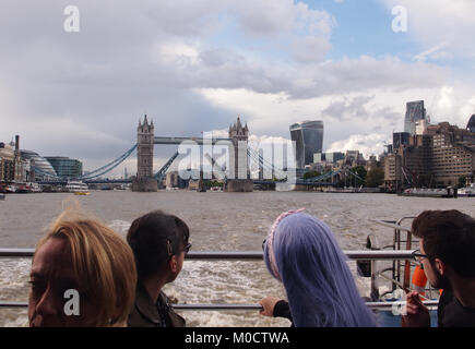 A view from the back of a Thames River passenger cruiser looking back to a raised Tower Bridge with four passengers - Stock Photo