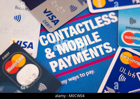 An assortment of credit and debit cards used for contactless and mobile payments - Stock Photo