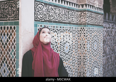 Arab woman in traditional clothing with red hijab in front of the wall with text from Koran - Stock Photo