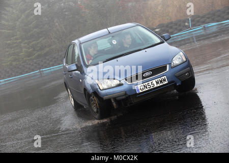 A young driver is given instruction on how to control a car during course at the skid pan centre at knockhill racing - Stock Photo