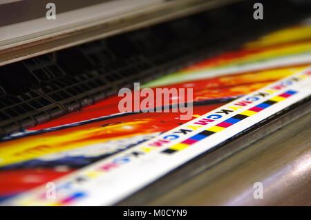 CMYK mark printed by inkjet plotter on white paper. Large digital printer machine. - Stock Photo
