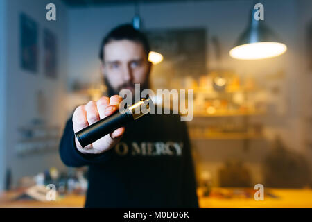 Young beard man show vaping device on his outstretched hand in camera. Selective focus. Vaping concept. Copy space. - Stock Photo