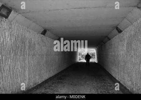 Looking through tunnel at figure in distance in black and white - Stock Photo