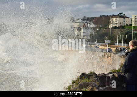 People watching from a safe location as waves crash against the sea wall during a stormy high tide at Torquay. - Stock Photo
