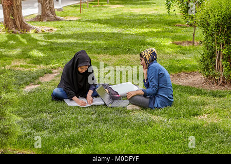 Isfahan, Iran - April 24, 2017: Two Muslim female students, dressed in Islamic hijab, are preparing for the exams, - Stock Photo