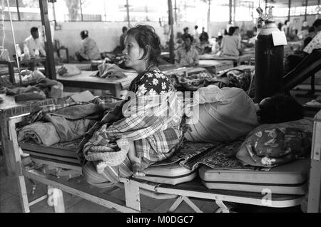 A woman cradles her baby whilst sitting on the bed of her critically ill husband in the in-patient ward at the Mae - Stock Photo