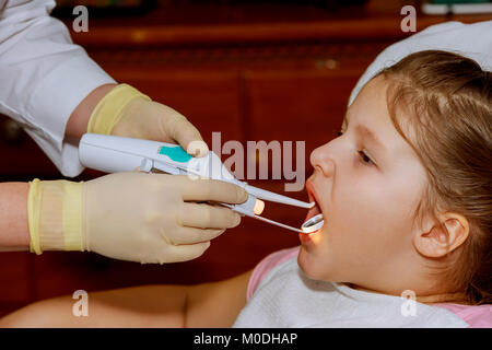 baby girl dentist examines the teeth of the patient cheerful child with curly red hair. girl smiling in dentist's - Stock Photo