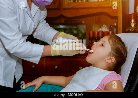 patient cheerful child with curly hair. girl smiling in dentist's chair. child mouth wide open in the dentist's - Stock Photo