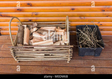 Basket of wood for making a fire and twigs on wooden deck background - Stock Photo