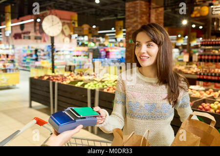 Woman Paying via Smartphone in Grocery Store - Stock Photo
